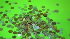 Монетки падая на зеленую предпосылку, замедленное движение акции видеоматериалы
