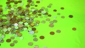 Монетки падая на зеленую предпосылку, замедленное движение видеоматериал