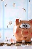 Монетки падая на копилку с штабелированным backgroun окон монеток Стоковое Изображение