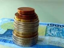 Монетки различного никеля и медного цвета штабелированные на бумажном счете стоковая фотография
