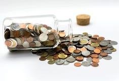 Монетки разливая из стеклянного опарника Стоковые Фото