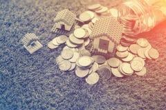 Монетки разливая из стеклянной бутылки и дома моделируют Стоковое Фото