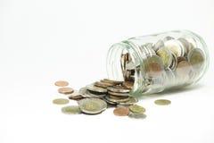 Монетки разливая из стеклянной бутылки на белой предпосылке Стоковые Изображения