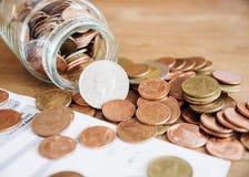 Монетки разливая из стеклянной бутылки с счетом Стоковые Фото