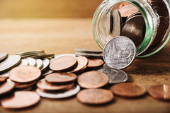 Монетки разливая из стеклянной бутылки Стоковое фото RF