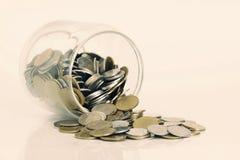 Монетки разливая из стеклянной бутылки Стоковое Фото