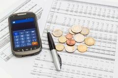 Монетки, ручка, smartphone в режиме калькулятора на таблице данных Стоковое Изображение RF