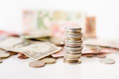 Монетки складывают и деньги стоковые изображения