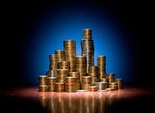 Монетки сложили на деревянном столе как башни города стоковое изображение rf