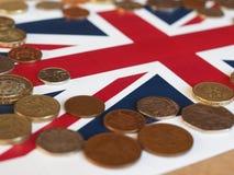 Монетки фунта, Великобритания над флагом Стоковые Изображения RF