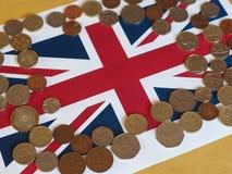Монетки фунта, Великобритания над флагом Стоковое Фото