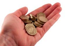 Монетки фунта в руке Стоковые Фото
