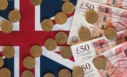 Монетки фунта и примечания, Великобритания над флагом Стоковое фото RF