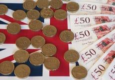 Монетки фунта и примечания, Великобритания над флагом Стоковое Фото