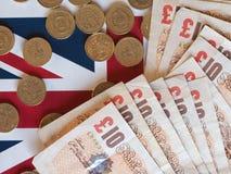 Монетки фунта и примечания, Великобритания над флагом Стоковая Фотография RF