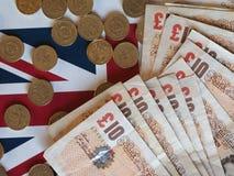 Монетки фунта и примечания, Великобритания над флагом Стоковые Изображения RF