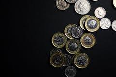Монетки фунта на черной предпосылке стоковое фото