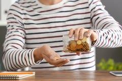 Монетки человека лить в стеклянный опарник на таблице стоковое изображение rf