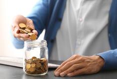 Монетки человека лить в стеклянный опарник на таблице стоковые изображения rf