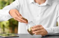 Монетки человека лить в стеклянный опарник на таблице стоковое фото rf