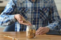Монетки человека лить в стеклянный опарник на таблице стоковые фотографии rf