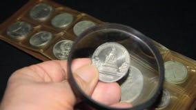 Монетки через крупный план лупы на черной предпосылке видеоматериал