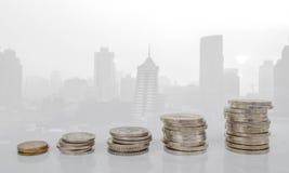 Монетки arragned как диаграмма на запачканном фото здания города Стоковая Фотография RF