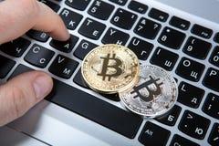 2 монетки bitcoin и человеческой руки на клавиатуре компьтер-книжки Стоковые Фото