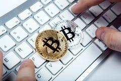 2 монетки bitcoin и человеческой руки на клавиатуре компьтер-книжки Стоковое Фото