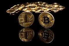 Монетки bitcoin и litecion Criptocurrency на черном зеркале отделывают поверхность рядом с золотыми монетками стоковое фото rf