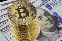 Монетки bitcoin металла на 100 предпосылках долларовых банкнот Стоковая Фотография RF