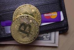 2 монетки bitcoin на бумажнике с долларами стоковое фото