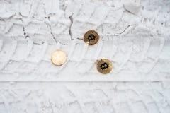 Монетки Copprito bitcoin золота лежат на снеге Никто В зиме на дороге, трассировки автомобилей стоковое изображение rf