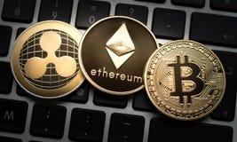 Монетки Cryptocurrencies Ethereum, пульсации, и Bitcoin на клавиатуре ноутбука компьютера стоковая фотография rf