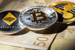Монетки Cryptocurrency над банкнотами евро; Bitcoin, Ethereum и Стоковое Изображение RF