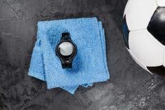 Монитор тарифа сердца на голубом полотенце около футбольного мяча стоковые изображения