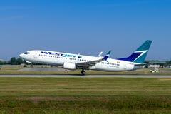 Монреаль, Квебек, Канада - 20-ое июля 2017: Боинг 737-800 Westjet принимает от международного аэропорта Pierre Elliott Trudeau стоковое фото rf