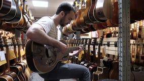 Монреаль, Квебек, Канада - 25-ое июня 2018: Счастливый покупатель выбрал гитару в магазине музыки сток-видео