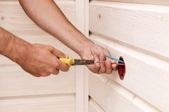 Монтаж электрического выхода на белой деревянной стене электриком стоковое фото rf