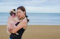 Мопс щенка собаки довольно сиротливым владением девушки Азии милый против пляжа, моря и предпосылки и улыбки голубого неба к каме Стоковые Изображения RF