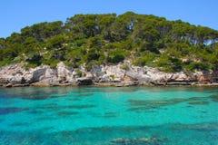 Море бирюзы в Менорке Испании Cala Caldana стоковые изображения