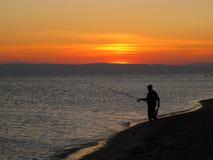 Море, вечер, заход солнца, рыболов на пляже Стоковые Изображения