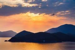 Море, горы и заход солнца Параплан в небе Стоковое Фото