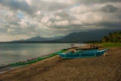 Море, горы и местные шлюпки на вулканическом пляже Pandan, остров Panay, Филиппины Стоковое Фото
