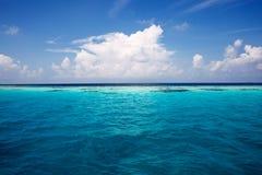 Море лета с волной открытого моря Взгляд рая глубокого прозрачного океана Безмятежность воды бирюзы и пушистых белых облаков Стоковые Фотографии RF