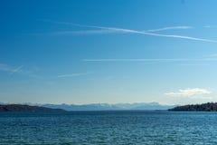 Море и голубое небо на солнечный день с горными вершинами в предпосылке на озере Starnberg около Мюнхена в Германии стоковое изображение