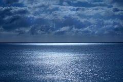 Море и небо в нижней половине спокойное темносинее море, на горизонте линия белый мерцающий накалять светлы от луны стоковое изображение rf