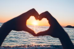 Море на заходе солнца с силуэтом рук Стоковое Изображение RF