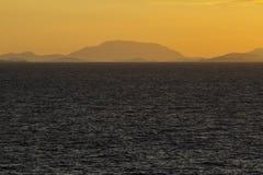 Море на заходе солнца с сценой горы Стоковые Изображения RF