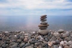 Море, небо, скалистый пляж и пирамида плоских серых камней Стоковые Изображения